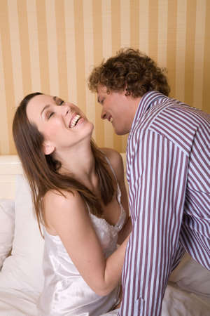 Young couple close together having fun dressing in the morning photo