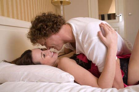 enamorados en la cama: Bonita pareja de j�venes se divierten en el dormitorio