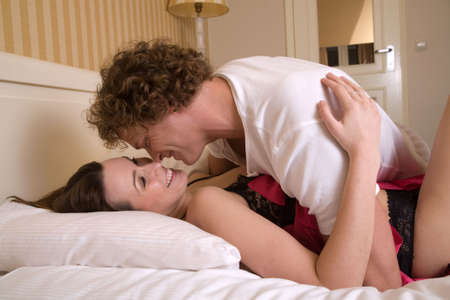 lovers in bed: Lovely young couple having fun in the bedroom