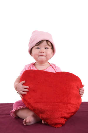 Cute baby holding a big red heart and wearing a small pink hat photo