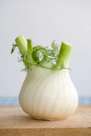 fennel: A whole fennel on a wooden chopping board