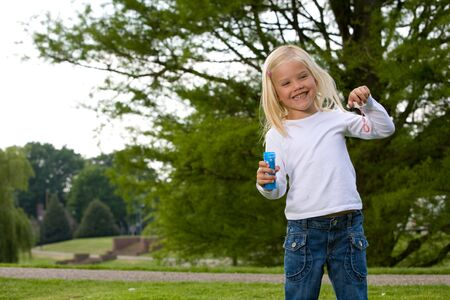 Cute blond four year old girl blowing bubbles Stock Photo - 3145047
