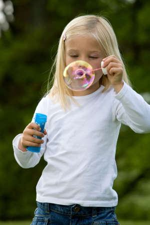 four year old: Cute four year old girl blowing a big soap bubble