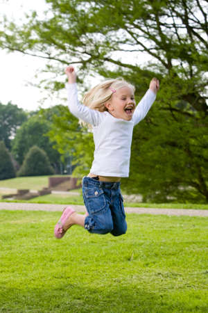 Cute blond four year old girl jumping in the park (some movement due to jumping)