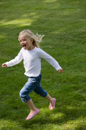 Four year old girl running across the field looking happy
