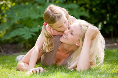 Pretty blond woman lying in the grass with her daughter, who is giving mum a kiss Stock Photo
