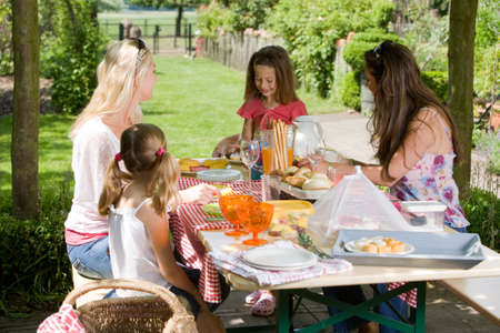 Mothers and their daughters having a picnic outdoors on a summer day photo