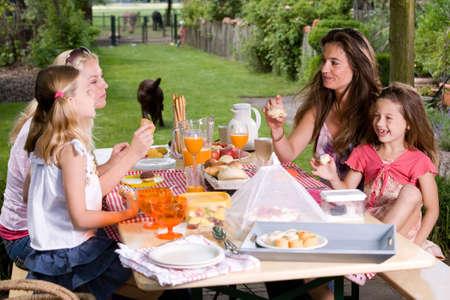 2 人の友人と彼らの娘、夏の屋外のピクニックを持っています。