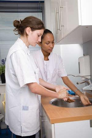 � fond: Deux jeunes �tudiants en m�decine � laver soigneusement les mains