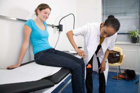 Arzt die Prüfung der Reflex ihrer Patienten, indem ihr auf die Knie Standard-Bild - 3257243