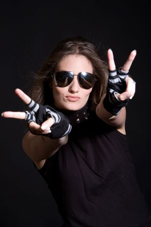 Beautiful brunette with sunglasses and a tough look giving the peace sign Stock Photo - 3257235