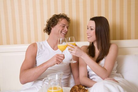 roomservice: Lovely young couple enjoying a simple breakfast in bed