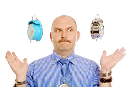 Man pulling a face while two alarm clocks are suspended above his hands photo