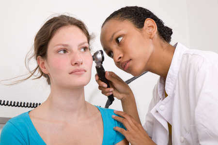 Doctor peering into her patients ear with an instrument Stock Photo - 3577335