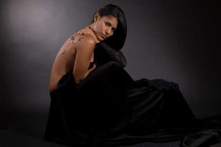 tatouage sexy: Beautiful br�silien femme envelopp�e dans de velours noir sur fond noir Banque d'images