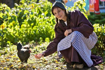 mujer arrodillada: Joven muchacha en la explotaci�n tradicional de las prendas de vestir de alimentaci�n de los pollos