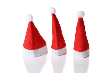pointy: Three cute red small santa hats on white background Stock Photo