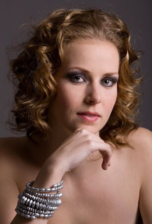 21: Beautiful young woman with curls in thoughtful pose Stock Photo