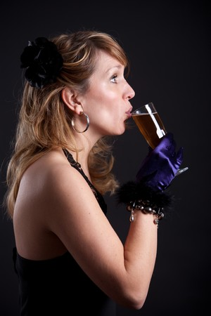 Pretty blond woman taking a sip from her glass photo