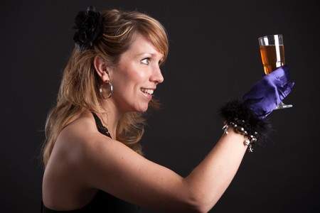 Prett blond girl holding a glass of sparkly wine giving a toast photo