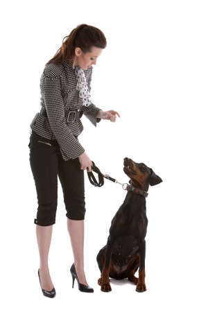 Pretty young woman directing her doberman pincher Stock Photo
