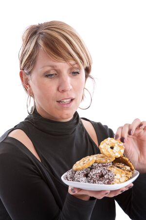 Attractive young woman taking a cookie from the plate photo