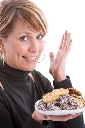 Woman holding up a plate of christmas cookies and making a yummy gesture photo
