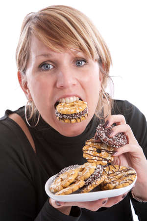 Attractive young woman with her mouth and hands full of cookies Stock Photo
