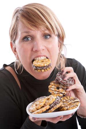 Attraktive junge Frau mit ihrem Mund und Hände voll von Cookies Standard-Bild - 4750827