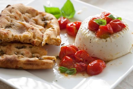Lunch with roasted ricotta and honey tomatoes served with focaccia bread photo