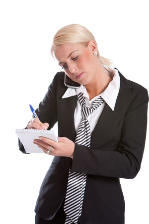 Beautiful business woman making notes while on the phone photo