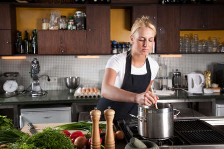checking ingredients: Pretty young woman working in a big kitchen Stock Photo