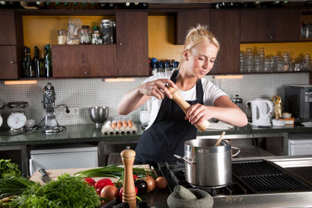 Pretty young woman working in a kitchen adding pepper