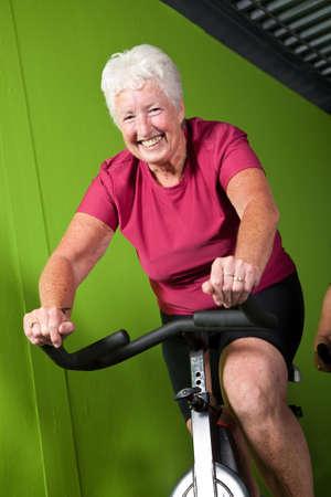 Aktive Senior Frau auf dem Fahrrad die Spinnerei in der Turnhalle Standard-Bild - 4952287