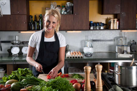 Pretty young blond female chef working in the kitchen Stock Photo - 5087038