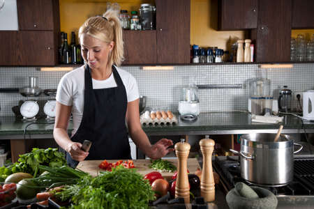 cutting boards: Pretty young female chef preparing the vegetables in the kitchen Stock Photo
