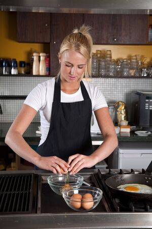 Pretty young female chef working in the kitchen breaking an egg Stock Photo - 5087132