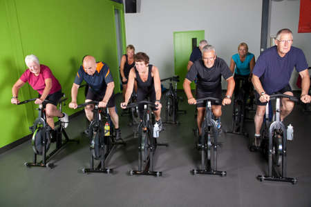 Group of fit mature adults in a spinning class photo
