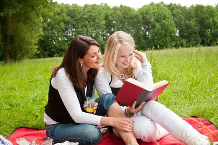 Mother and daughter outdoors on a picnic blanking reading together Stock Photo - 5087047