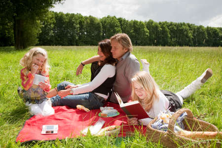 Pretty young family enjoying an outdoors picnic together in the field photo