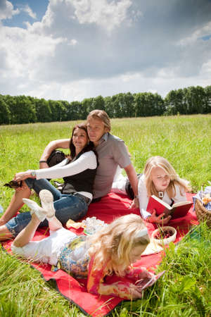 Beautiful young family with two daughters enjoying an outdoors picnic Stock Photo