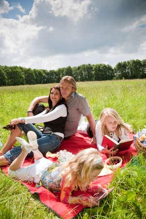 Schöne junge Familie mit zwei Töchtern genießen ein Picknick im Freien Standard-Bild - 5087043