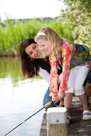 Cute young girl trying to catch a fish with mom watching over her