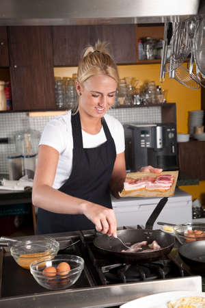 Pretty blond girl in the kitchen frying the bacon