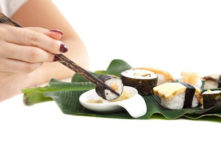 Woman hand holding a sushi roll with chopsticks photo
