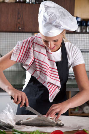 Pretty young female chef cleaning the trout Stock Photo - 5213084