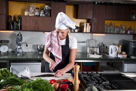 maldestro: Donne chef prepara a tagliare la testa della trota Archivio Fotografico