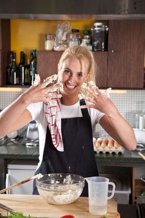 Beautiful female chef getting her hands dirty in the dough Stock Photo - 5213081