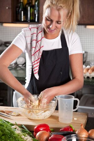 Pretty blond woman kneading the dough in the kitchen photo