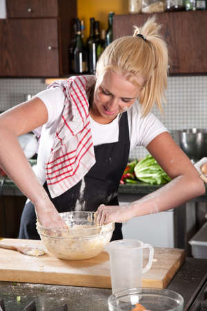Female chef getting flour all over her self while kneading the dough Stock Photo - 5213085